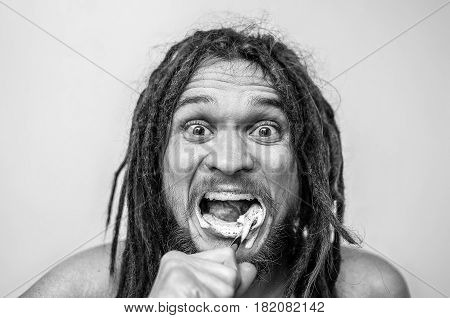 A guy with a dreadlocks cleans his teeth. Emotion on a black and white photo