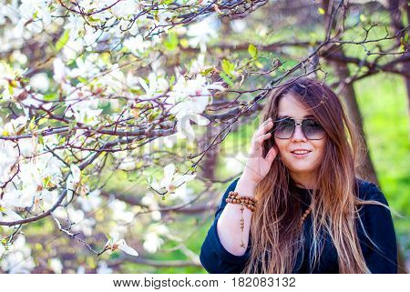 A beautiful woman in sunglasses laughs in a blooming garden. Fat girl near blooming trees. Beautiful girl with long hair wearing sunglasses. Happy girl smiling.