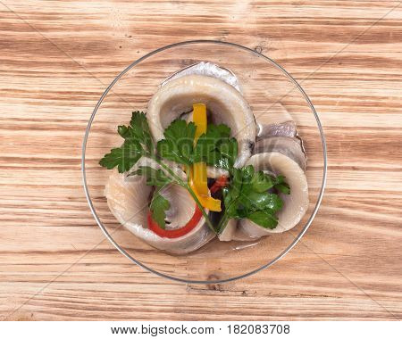 Matjes herring fillets in oil with parsley on clear plate and wooden vintage tray