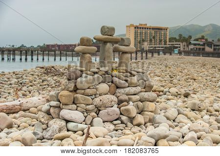 Stone crosses made of balanced rock on Ventura beach with buildings in background.