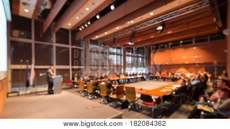 Speaker giving a talk on corporate business event. Audience at the conference hall. Business and Entrepreneurship event. Out of focus image. Unrecognizable business people.