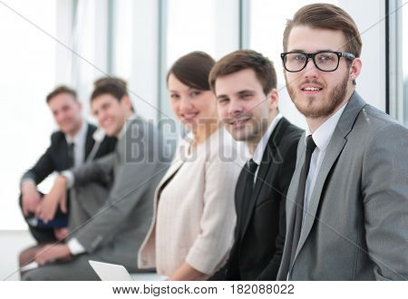 Smiling and confident business team having time break in front o