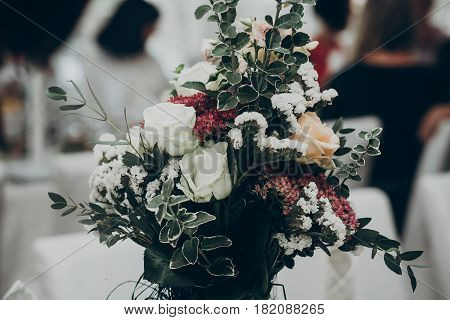 stylish rustic bouquet on table at wedding reception. space for text. floral arrangements and decor. luxury life and wedding reception. expensive catering