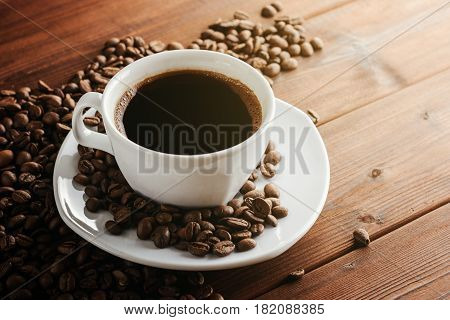 Coffee cup with saucer and beans on wooden table. Selective focus.