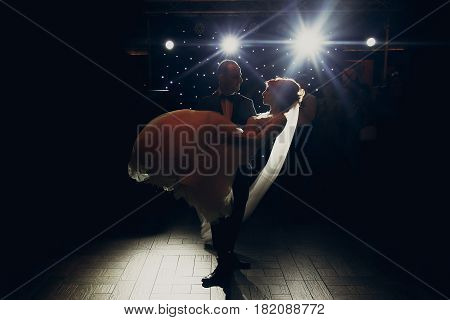 Stylish Groom Lifting Happy Bride And  Dancing At Wedding Reception In Light. Gorgeous Wedding Coupl