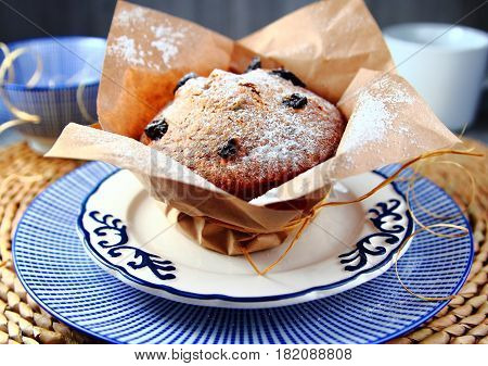 cupcake with raisins and powdered sugar on a blue dish