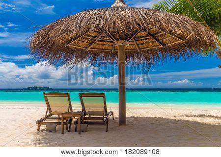 Dreamy beach with sun loungers under a beach umbrella at Maldives