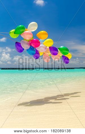 Bunch of colorful balloons flying over tropical ocean