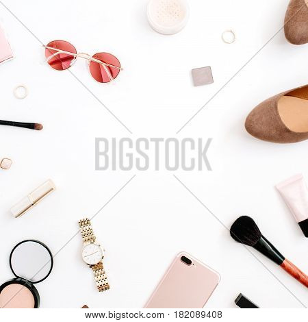 Beauty blog fashion frame concept. Female pink styled accessories: mobile phone watches sunglasses cosmetics shoes on white background. Flat lay top view trendy feminine background.