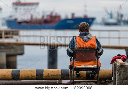 Maritime transportation industry. Roustabout leisure time sits on the embankment and looking at ships.