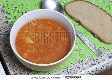 Preparation Of Tomato Soup. The Soup Poured Into The Cup Cools On The Table. Nearby Is A Spoon And A