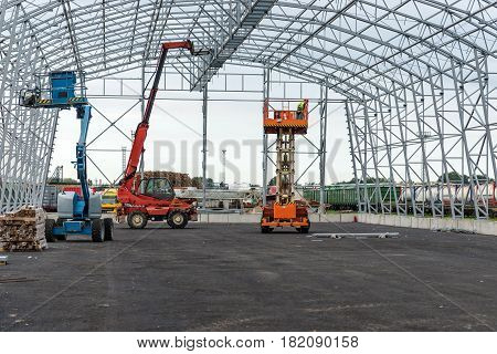 Lift with platform work in warehouse hangar construction field.