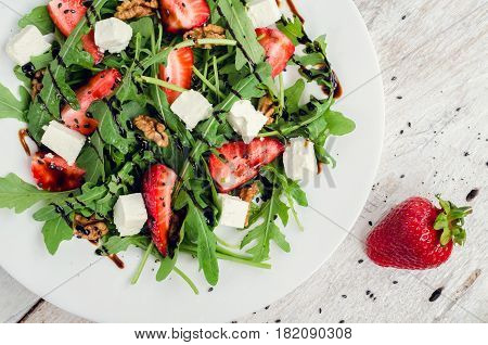 Fresh salad with arugula strawberries feta cheese nuts black sesame seeds and balsamic glasse sauce served on white plate on rustic wooden table. Healthy organic diet food concept. Top view.