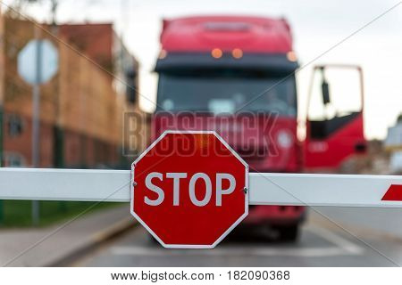 Maritime transportation industry. Truck standing at the barrier with a STOP sign.