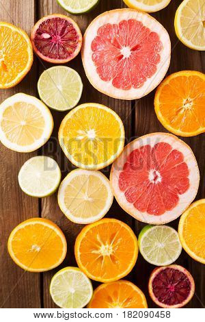 Citrus fruits on a wooden background. Оrange lemon grapefruit mandarin lime. Mixed festive colorful tropical and citrus fruit sliced. Healthy eating photo concept. Copyspace
