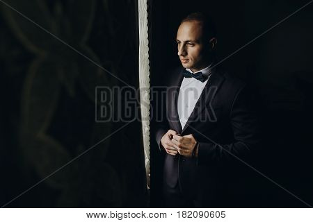 Stylish Groom Portrait At The Window While Getting Ready In The Morning For Wedding Ceremony. Luxury
