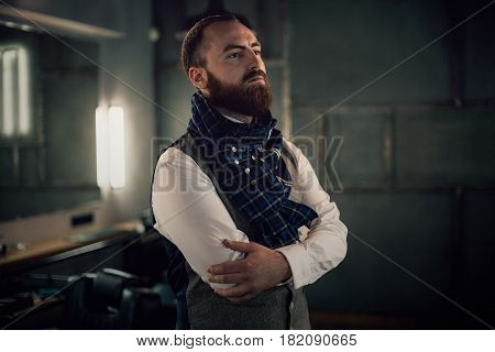 Handsome bearded man hipster with stylish beard in white shirt and chekered scarf standing with serious face in beauty salon or barbershop