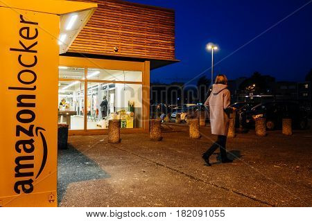 PARIS FRANCE - FEB 15 2017: Woman leaving Amazon locker orange delivery package locker at dusk - Amazon Locker is a self-service parcel delivery service offered by online retailer Amazon.com