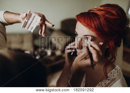 Beautiful Stylish Bride With Red Hair Talking On Phone And Smiling, Wearing Robe,  Getting Make Up A