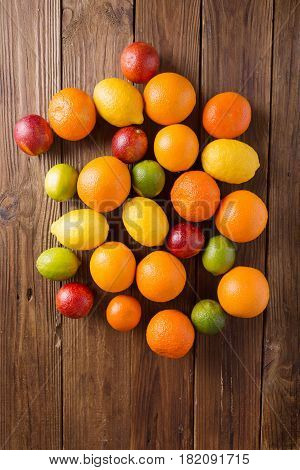 Orange and lemon lime sicilian orange on a wooden background. Citrus fruits. Mixed festive colorful tropical and citrus fruit. Healthy eating photo concept. Copyspace