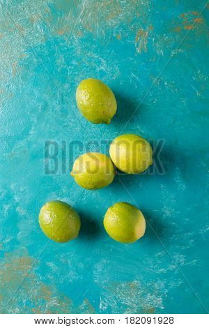 Limes on a turquoise abstract background. Lime. Citrus fruits. Mixed festive colorful tropical and citrus fruit. Healthy eating photo concept. Copyspace
