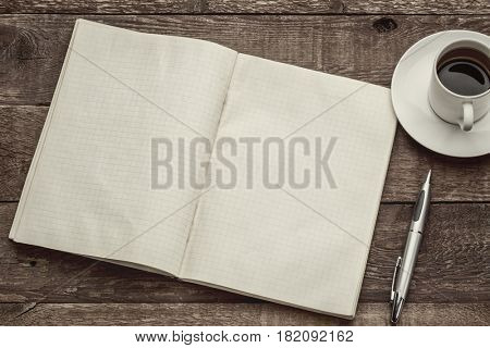 old blank notebook opened on a  rustic  barn wood table with a cup of coffee, sepia toned