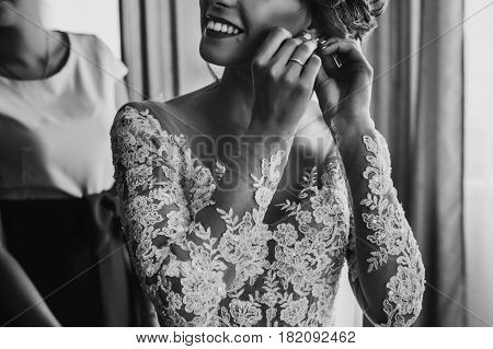 Stylish Happy Bride Putting On Earrings And Smiling, Rustic Wedding Morning Preparation In Home. Bri