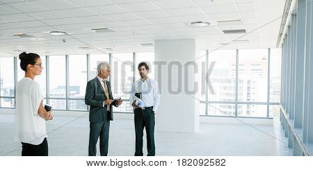 Business people standing at empty space discussing the interior of office with architect. Real estate agent talking with potential clients inside an empty office space.