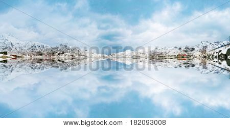 Reflection of mountains in the snow and clouds in the lake