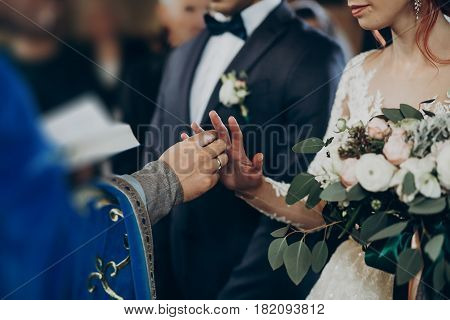 Wedding Couple Putting On Wedding Rings At Matrimony In Church. Stylish Bride And Groom Kissing And