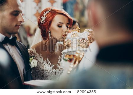 Happy Bride And Stylish Groom Kissing Crowns And Baptizing During Wedding Ceremony. Wedding Couple A