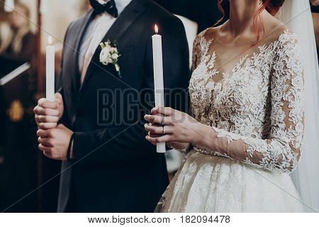 Happy Bride And Stylish Groom Holding Candles With Light During Wedding Ceremony. Wedding Couple At