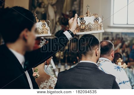 Happy Bride And Stylish Groom Under Crowns And Baptizing During Wedding Ceremony. Wedding Couple At