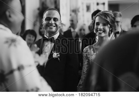 Wedding Couple Holding Hands And Smiling At Matrimony Wedding Ceremony In Church. Stylish Bride And
