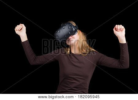 Blonde girl using VR - virtual reality headset isolated on black background