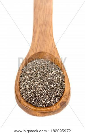 Whole dried black chai seeds in wooden spoon on white background