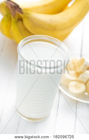 Yogurt with fresh bananas on white wooden background closeup healthy breakfast