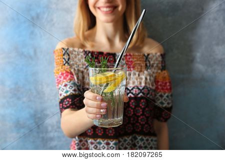 Young woman with lemonade on color background, closeup