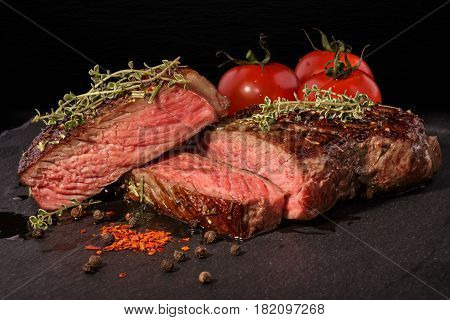 Sliced grilled beef steak with spices on slate slab on dark background