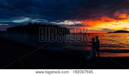 Silhouettes of couples near Sveti Stefan island in Montenegro