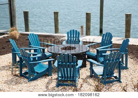 A very relaxing fire pit set up with wood chairs on the waterfront