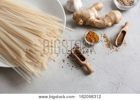 Plate with rice noodles and spices on table