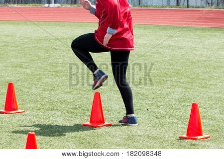 A track and field athlete does speed form drills over orange cones on a green turf field