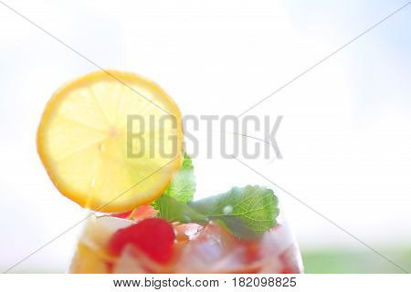 Icy drink of white wine with fresh berries mint and lemon with copy space