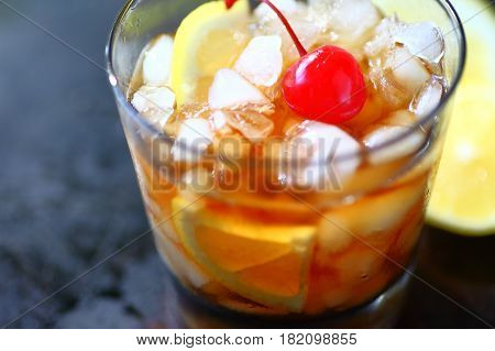 Closeup of whiskey sour cocktail with crushed ice lemon and maraschino cherry with copy space