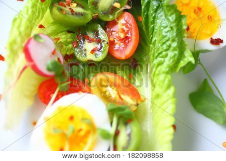 Overhead of whole romaine leaves with cherry tomatoes baby kiwifruit boiled egg halves pea sprouts radishes and hot pepper flakes