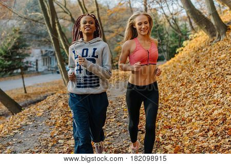Pretty attractive women running in autamn park. Blonde and african girls have training in the morning. Female smiling. Golden leaves around