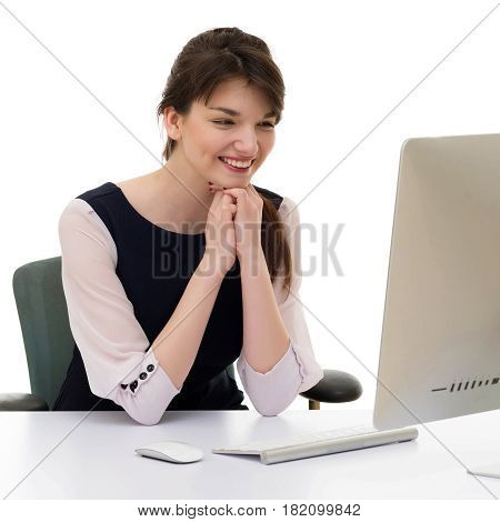 Portrait of young pretty business woman in white and blue suit looking on screen of computer monitor sitting at her workplace in office.