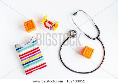 children's doctor work with stethoscope and toys on white desk background top view