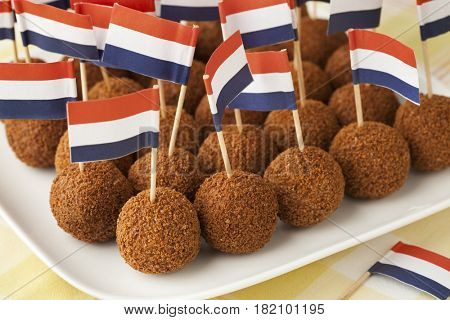 Dutch traditional snack bitterballen on a dish with a dutch flag cocktail stick